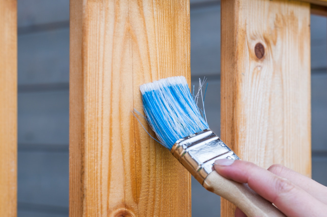 Picture of applying wood stain to a deck railing using a brush