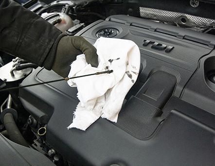Photo of Mechanic Checking Motor Oil Dipstick